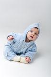 Blue baby in a studio. Baby in blue outfit looking happily in a studio Royalty Free Stock Image