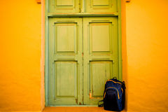Blue back pack near the green door and yellow wall Royalty Free Stock Photo