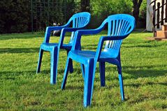 Blue back yard lawn chairs surrounded by a garden Stock Images