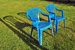 Blue back yard lawn chairs surrounded by a garden Stock Photo