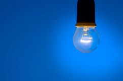 Blue Background. Close up of light bulb against blue background - shallow depth of field Royalty Free Stock Image