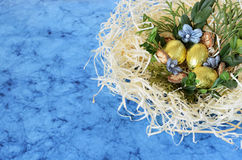 Golden chocolate eggs in the nest. Blue background with arrangement with golden eggs and nest in the corner Royalty Free Stock Image