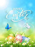 Blue background with butterflies and three Easter eggs in grass Royalty Free Stock Photography