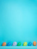 Blue background with colored balloons in row Royalty Free Stock Images