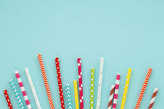 Blue background with colorful paper straws for cocktails. Stock Images