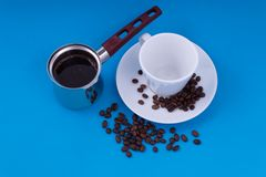On the blue background is an empty mug with a saucer to the left of the vessel with freshly brewed coffee stock photos