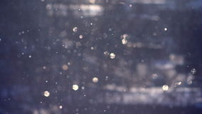 A blue background of falling snow in the rays of the sun stock video