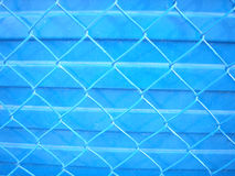 Blue background and fence. Chain link fence and shadows with blue background Stock Photo