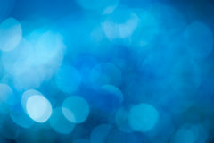 Blue background. Blue festive New Years background. Abstract with bright twinkles, sparkles, blurred, defocused light Stock Photos