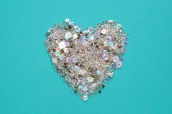 Blue background with heart of sequins and beads Stock Images