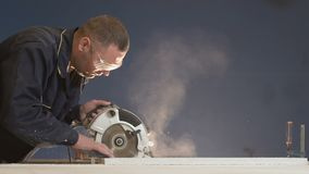 20s Man in Overalls on Blue Background Processes Large Bar with Saw Slow Motion. On a blue background, a lot of wood shavings lie from the bar. A worker with a stock video footage