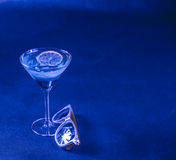 Blue background, mixed drink, lemon, martini glass, yellow sungl Royalty Free Stock Image