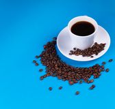 On a blue background, a mug of coffee next to it is filled with coffee beans in the shape of a crescent royalty free stock image