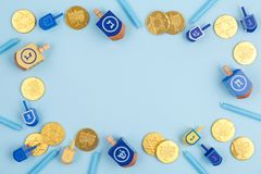Blue background with multicolor dreidels, menora candles and chocolate coins. Hanukkah and judaic holiday concept. royalty free stock photos