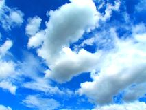 Clear blue sky with fluffy clouds stock images