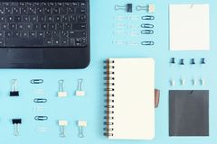 On a blue background, the office supplies are neatly arranged. In the corner is a black laptop. Empty notebook on the. Springs with space for text. Beautiful royalty free stock image