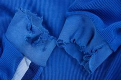 Blue fabric texture with torn sleeves on old clothes. Blue background of a piece of cloth with torn sleeves on old clothes Stock Photo