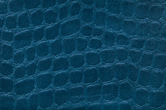 Blue background from a soft upholstery textile material, closeup. Fabric with pattern imitating crocodile skin.. Royalty Free Stock Photography