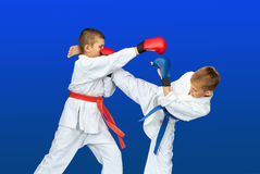 On a blue background sportsmens beat karate blows Royalty Free Stock Photography