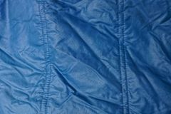 Blue texture of synthetic fabric from a fragment of crumpled clothes Royalty Free Stock Image