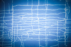 Blue background with white chaotic cracks. Toned Stock Image