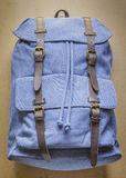 Blue backpack with leather elements on wood board. Background Royalty Free Stock Image