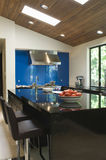 Blue Backsplash In Modern Kitchen. Blue backsplash and breakfast bar in modern kitchen royalty free stock images