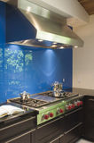 Blue Backsplash And Stainless Steel Vent Hood. In modern kitchen royalty free stock image