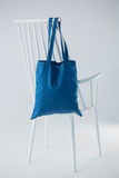 Blue bag hanging on a white chair Royalty Free Stock Image
