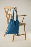 Blue bag hanging on a wooden chair Royalty Free Stock Image