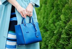 Blue bag and scarf in female hands. close-up. Woman in coat and in a striped dress. outdoors. Girl with a bright stylish