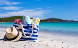Blue bag, straw hat, flip flops and towel on white. Beach bag, straw hat, towel on the white sandy tropical beach Stock Images