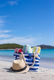 Blue bag, straw hat, flip flops and towel on white. Beach bag, straw hat, towel on the white sandy tropical beach Stock Photo