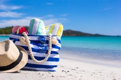 Blue bag, straw hat, flip flops and towel on white. Beach bag, straw hat, towel on the white sandy tropical beach Stock Image