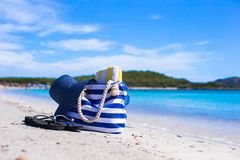 Blue bag, straw hat, flip flops and towel on white. Beach bag, straw hat, towel on the white sandy tropical beach Royalty Free Stock Photo