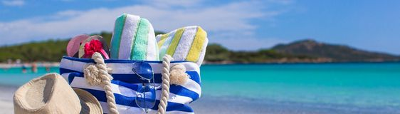 Blue bag, straw hat, flip flops and towel on white. Beach bag, straw hat, towel on the white sandy tropical beach Stock Photos