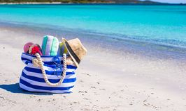 Blue bag, straw hat, flip flops and towel on white. Beach bag, straw hat, towel on the white sandy tropical beach Stock Photography