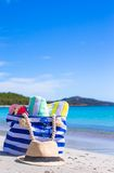 Blue bag, straw hat, flip flops and towel on white. Beach bag, straw hat, towel on the white sandy tropical beach Royalty Free Stock Images