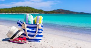 Blue bag, straw hat, flip flops and towel on white. Beach bag, straw hat, towel on the white sandy tropical beach Royalty Free Stock Photography