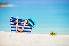 Blue bag, straw hat, sunglasses on white beach Royalty Free Stock Photography
