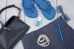 With blue bag, sunglasses, flip flops, nail polish and little airplane on white wooden background. Travel concept - summer women& x27;s fashion with blue bag royalty free stock image
