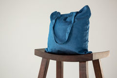 Blue bag on wooden stool Royalty Free Stock Photo