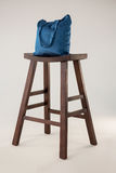 Blue bag on wooden stool Royalty Free Stock Photography