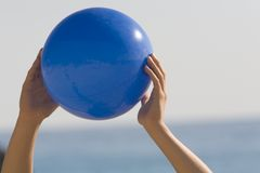 Blue ball. In the hands Stock Photography