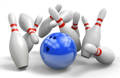 Blue ball hitting a perfect strike on ten-pin bowling. Bowling bowl knocking down 10 pins in a strike Royalty Free Stock Images
