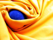 Blue ball of iron in yellow blanket. royalty free stock images