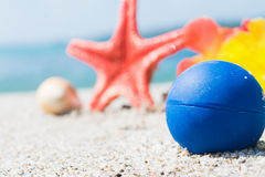 Blue ball and objects on the sand Stock Photos