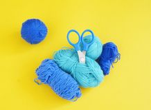 Blue ball of woollen thread. Yellow background. The view from the top. Threads, wool, blue and turquoise colors with a pair of scissors. Material for a hobby Royalty Free Stock Photos