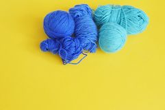 Blue ball of woollen thread. Yellow background. The view from the top. Threads, wool, blue and turquoise colors with a pair of scissors. Material for a hobby Stock Images