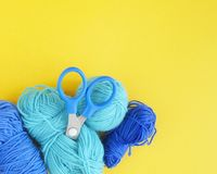 Blue ball of woollen thread. Yellow background. The view from the top. Threads, wool, blue and turquoise colors with a pair of scissors. Material for a hobby Royalty Free Stock Photography
